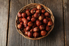 Hazelnuts in basket on brown wooden background. Stock Images