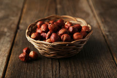 Hazelnuts in basket on brown wooden background Royalty Free Stock Photos