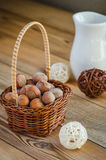 Hazelnuts in the basket. Hazelnuts in a small basket and white jug Royalty Free Stock Image