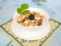 Hazelnuts and blackberries with cream. Stock Image