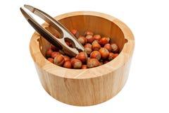 Hazelnuts in bowl isolated on white background. Hazelnuts and nutcracker  in bowl isolated on white background stock image