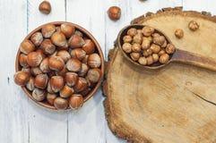 Hazelnuts in a bowl near a spoon peeled walnut on a wooden surfa Royalty Free Stock Photos