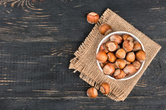 Hazelnuts in bowl. Bowl with raw hazelnuts in shell on sackcloth and table, top view Royalty Free Stock Images