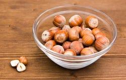 Hazelnuts on bowl on wood Stock Images
