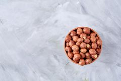 Hazelnuts in ceramic bowl on wihite background with copy space, top view, selective focus. Hazelnuts in clay ceramic bowl on white textured background with copy stock image
