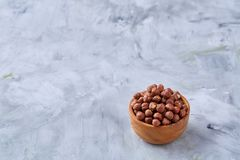 Hazelnuts in ceramic bowl on wihite background with copy space, top view, selective focus. Hazelnuts in clay ceramic bowl on white textured background with copy royalty free stock photos