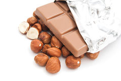 Hazelnuts and chocolate on white. Hazelnuts and chocolate bar closeup on white royalty free stock photo