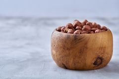 Hazelnuts in ceramic bowl on wihite background with copy space, top view, selective focus. Hazelnuts in clay ceramic bowl on white textured background with copy royalty free stock photo
