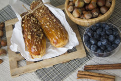 Hazelnuts and creampuffs. French eclairs with various nuts. Closeup food photo Stock Image
