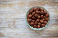 Hazelnuts in a glass jar in the background of the tree. Copy space. royalty free stock photo