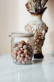 Hazelnuts in a glass jar. A vase in the background Royalty Free Stock Photography