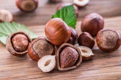 Hazelnuts i hazelnut opuszczają na drewnianym stole zdjęcia royalty free