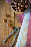 Hazelnuts In Bowl And Nut Cracker On Cloth Royalty Free Stock Images