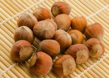 Hazelnuts. A lot of hazelnuts close-up on a bamboo mat stock photography