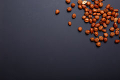 Hazelnuts, nuts used to make praline, and also used in combination with chocolate on a violate background, copy space. Hazelnuts, nuts are are rich in protein Royalty Free Stock Photo