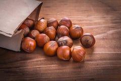 Hazelnuts paperbag on vintage wooden board food Stock Photo