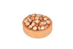 Hazelnuts in pot. Hazelnut shells in pot isolated on white Royalty Free Stock Photography