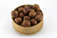 Hazelnuts in a round wooden form. On a white background Royalty Free Stock Photography