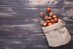 Hazelnuts in the sack on brown wooden table royalty free stock images