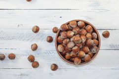 Hazelnuts in shell in brown clay bowl, top view Stock Images
