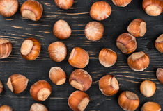Hazelnuts in shell. Scattered raw hazelnuts in shell on a wooden background, top view Stock Image