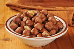 Hazelnuts. A small bowl of hazelnuts on a rustic wooden table Stock Photos