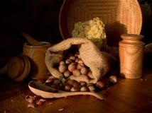 Hazelnuts Still Life. Still life includes huzelnuts wood spoon kegs wicker on a table Stock Photos