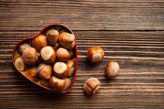 Hazelnuts w serce kształtnej blaszanej puszce Zdjęcia Royalty Free