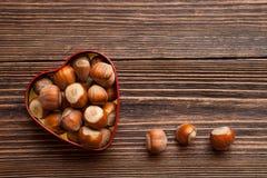 Hazelnuts w serce kształtnej blaszanej puszce Obrazy Stock