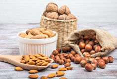 Hazelnuts, walnuts, almonds on gray wooden background Royalty Free Stock Photography