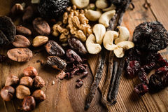 Hazelnuts, walnuts, cashews and vanilla orchid pod. On the grunge table or desk in the kitchen. Composition of the ingredients for cooking cakes or ice cream royalty free stock images