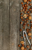 Hazelnuts, walnuts and nutcracker on gray wooden background. Royalty Free Stock Photography
