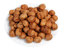 Hazelnuts on a white plate, isolated. Stock Images