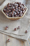 Hazelnuts in a wicker basket. Nuts in a wicker basket on an old table covered with burlap Stock Photo