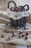 Hazelnuts in wicker basket on the table covered burlap. Royalty Free Stock Photos