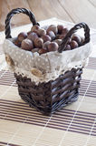 Hazelnuts in wicker basket on the table. Hazelnuts in wicker basket on the table laying napkins made of straw Stock Image