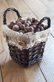Hazelnuts in wicker basket on the wooden table. Vertical Royalty Free Stock Images