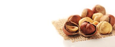 Hazelnuts on wicker and white background Royalty Free Stock Photos