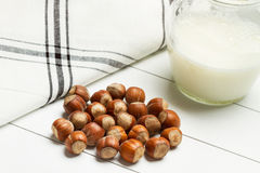 Hazelnuts in a wood bowl. And a jar of milk Royalty Free Stock Images