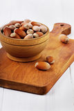 Hazelnuts in a wooden bowl. On a brown board Stock Photo
