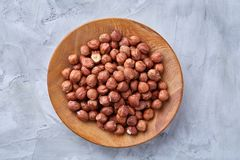 Hazelnuts in wooden bowl on wihite background with copy space, top view, selective focus. Hazelnuts in wooden bowl on white textured background with copy space stock image