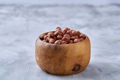 Hazelnuts in wooden bowl on wihite background with copy space, top view, selective focus. Hazelnuts in wooden bowl on white textured background with copy space stock photo