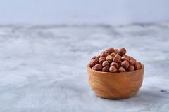 Hazelnuts in wooden bowl on wihite background with copy space, top view, selective focus. Hazelnuts in wooden bowl on white textured background with copy space stock photos