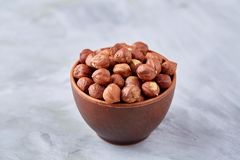 Hazelnuts in wooden bowl on wihite background with copy space, top view, selective focus. Hazelnuts in wooden bowl on white textured background with copy space royalty free stock images