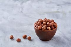 Hazelnuts in wooden bowl on wihite background with copy space, top view, selective focus. Hazelnuts in wooden bowl on white textured background with copy space stock images