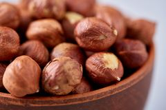 Hazelnuts in wooden bowl on wihite background with copy space, top view, selective focus. Hazelnuts in wooden bowl on white textured background with copy space royalty free stock photos