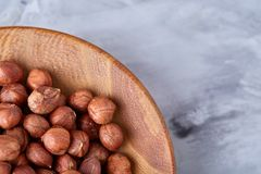 Hazelnuts in wooden bowl on wihite background with copy space, top view, selective focus. Hazelnuts in wooden bowl on white textured background with copy space royalty free stock image