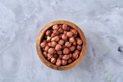 Hazelnuts in wooden bowl on wihite background with copy space, top view, selective focus. Hazelnuts in wooden bowl on white textured background with copy space stock photography