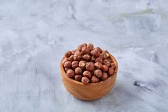 Hazelnuts in wooden bowl on wihite background with copy space, top view, selective focus. Hazelnuts in wooden bowl on white textured background with copy space royalty free stock photography