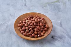 Hazelnuts in wooden plate on wihite background with copy space, top view, selective focus. Hazelnuts in wooden plate on white textured background with copy royalty free stock images